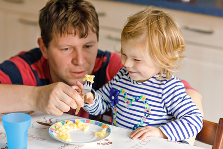 Adorable baby girl eating noodle, pasta macaroni. Father helping daughter learning to use spoon. Cute healthy toddler child sitting in highchair, learning to eat by itself with dad in domestic kitchen Stock Photo