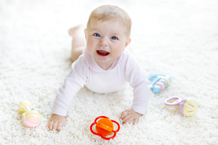 Cute baby girl playing with colorful pastel vintage rattle toy