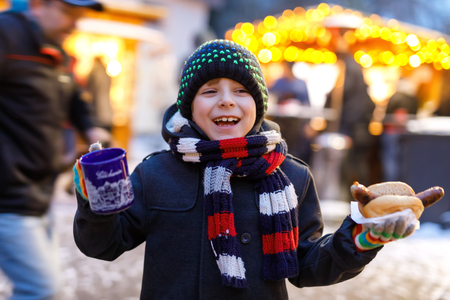 Little cute kid boy eating German sausage and drinking hot children punch on Christmas market Фото со стока