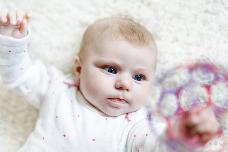 Cute baby girl playing with colorful rattle toy