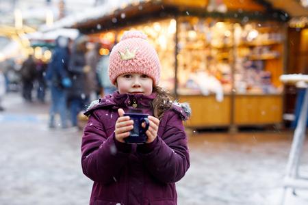 Little kid girl with hot chocolate on Christmas market Stock Photo