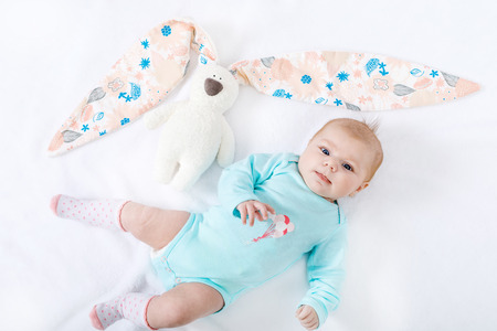 Adorable cute newborn baby girl with Easter bunny toy