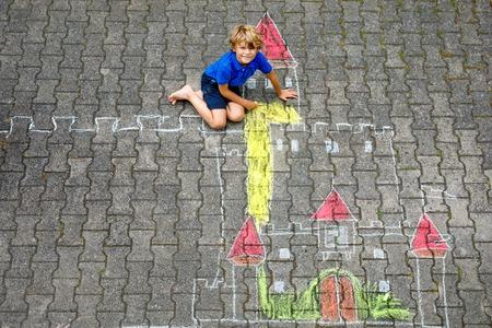 Piccolo ragazzo del bambino che disegna il castello e la fortezza del cavaliere con i gessi colorati. Felice bambino in età prescolare divertendosi con la creazione di un'immagine di gesso. Tempo libero creativo per bambini e ragazzi in estate