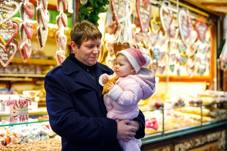 Middle aged father holding baby daughter girl near sweet stand with gingerbread and nuts. 스톡 콘텐츠