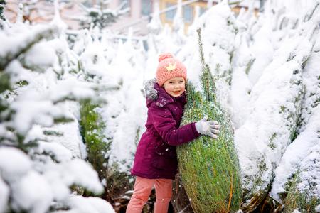 Cute little smiling kid girl on christmas tree market.