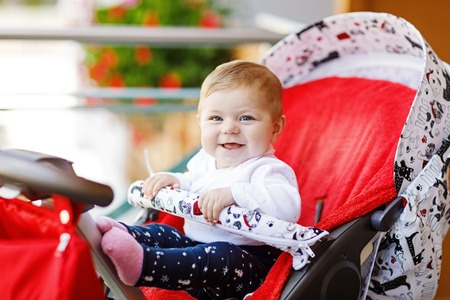 Cute little beautiful baby girl sitting in the pram or stroller and waiting for mom. Happy smiling child with blue eyes.