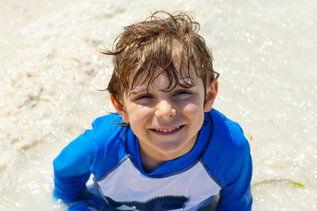 little blond kid boy having fun on tropical beach of Jamaica Stock Photo
