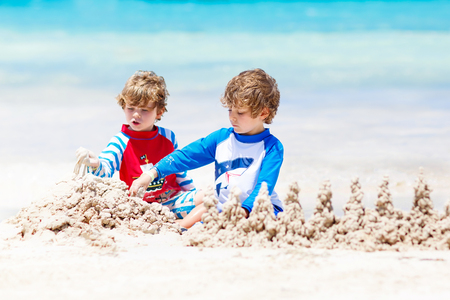 Two kid boys building sand castle on tropical beach of Boracay, Philippines