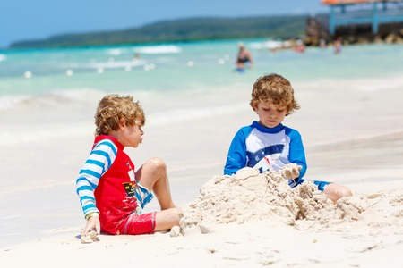 Two little kids boys having fun with building a sand castle on tropical beach of carribean island.
