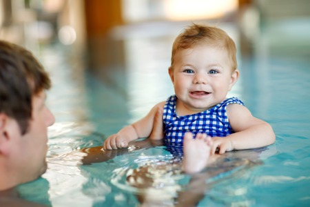 Happy middle-aged father swimming with cute adorable baby girl in swimming pool. 写真素材