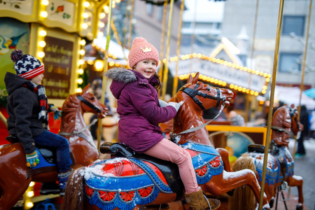 Adorable little kid girl riding on a merry go round carousel horse at Christmas funfair or market, outdoors. Happy child having fun on traditional family xmas market in Munich, Germany 스톡 콘텐츠