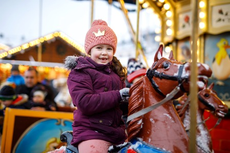 Adorable little kid girl riding on a merry go round carousel horse at Christmas funfair or market, outdoors. Happy child having fun on traditional family xmas market in Nuremberg, Germany Stok Fotoğraf - 110847077