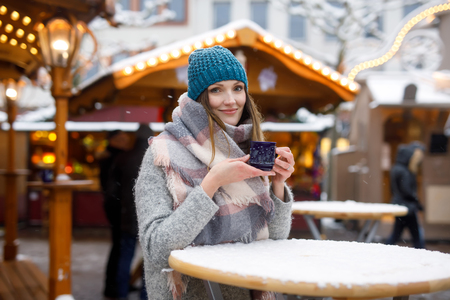 Beautiful young woman drinking hot punch, mulled wine on German Christmas market. Happy girl in winter clothes with lights on background on winter snow day in Leipzig, Germany. Stok Fotoğraf - 110847104
