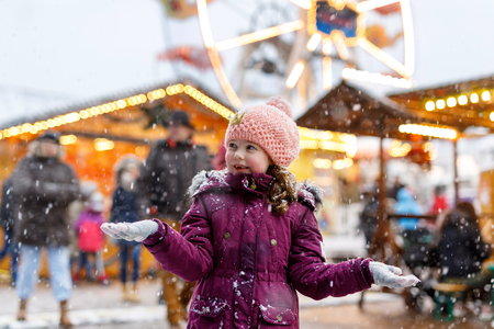 Little cute kid girl having fun on traditional German Christmas market during strong snowfall.. Happy child enjoying traditional family market in Germany, Frankfurt. Laughing girl in colorful clothes..
