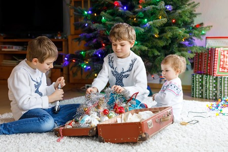 Two little kid boys and adorable baby girl decorating Christmas tree with old vintage toys and balls. Family preaparation celebration of family feast. Children, brothers and sister in festive clothes.