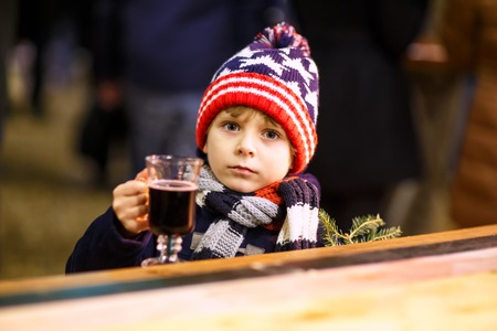 Little cute kid boy with cup of steaming hot chocolate or children punch. Happy child on Christmas market in Germany. Preschool kid in winter clothes warming hands on cup and drinking eggnog. Stock Photo
