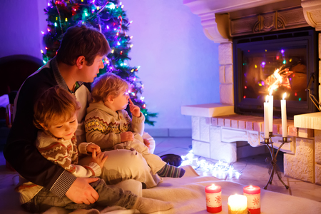 Father and two little toddler boys sitting by chimney, candles and fireplace and looking on fire. Family celebrating Christmas. With Xmas tree and lights on background. Kids happy about gifts..