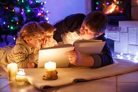 Padre y dos niños pequeños leyendo un libro junto a la chimenea, velas y chimenea. Familia celebrando la Navidad. Con árbol de Navidad y luces de fondo. Niños felices con libros y regalos.
