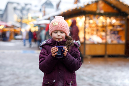 Little cute kid girl with cup of steaming hot chocolate or children punch. Happy child on Christmas market in Germany. Traditional leisure for families on xmas. Stock Photo