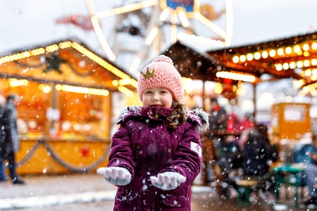 Little cute kid girl having fun on traditional Christmas market during strong snowfall. Happy child enjoying traditional family market in Germany. Laughing girl in colorful clothes. Standard-Bild
