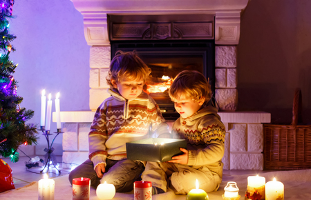 Two little children sitting by a fireplace at home on Christmas time. Happy cute adorable toddler boys, blond twins opening surprise gift box. Family celebrating xmas holiday Reklamní fotografie