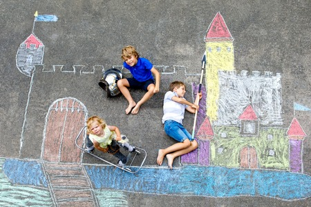 Two little kids boys and cute toddler girl drawing knight castle with colorful chalks on asphalt. Happy siblings and friends having fun with creating chalk picture and painting.