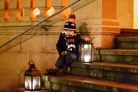 Little cute kid boy with with a light lantern on stairs near church. Happy child on Christmas market in Germany. Kid waiting on parents on cold winter day. Stock Photo