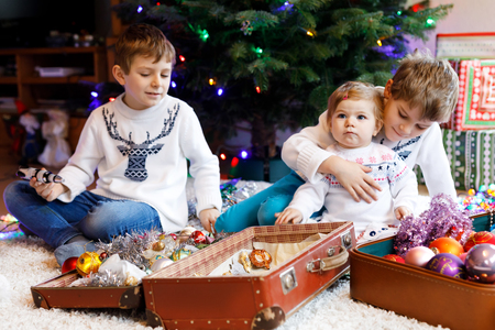Two little kid boys and adorable baby girl decorating Christmas tree with old vintage toys and balls. Family preaparation celebration of family feast. Children, brothers and sister in festive clothes Stock Photo