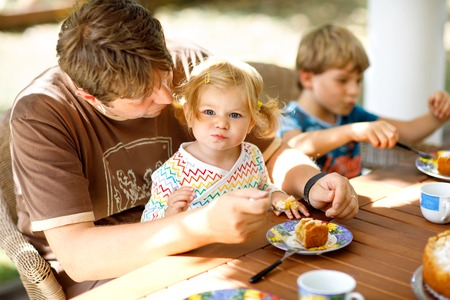 Young middle-aged father feeding cute little toddler girl in restaurant. Kid boy eating on background. Happy healthy family in an outdoor cafe in summer time, eating cake.