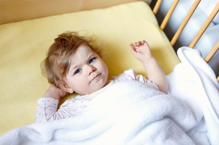 Cute little baby girl lying in cot before sleeping. Happy calm child in bed. Going sleep. Peaceful and smiling child looking on parents. Going to bed alone.