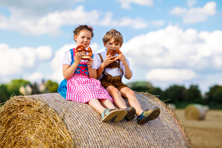 Two kids in traditional Bavarian costumes in wheat field. German children eating bread and pretzel during Oktoberfest. Boy and girl play at hay bales during summer harvest time in Germany Standard-Bild - 110888007