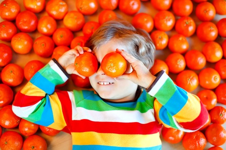 Adorable little kid boy with mandarin oranges background. Happy smiling child having fun with lot of fruits. Healthy food, eating and lifestyle concept.