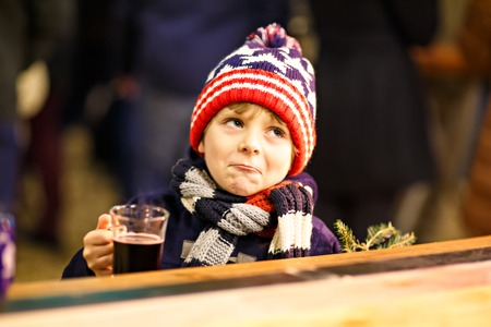 Little cute kid boy with cup of steaming hot chocolate or children punch. Happy child on Christmas market in Germany. Preschool kid in winter clothes warming hands on cup and drinking eggnog
