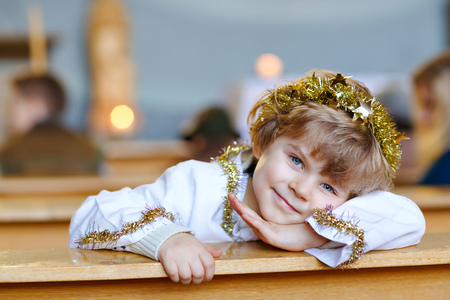 Beautiful little kid boy playing an angel in Christmas story in a church. Happy adorable blond child with lights and xmas tree on background. Celebration of Xmas eve, big christian, catholic holiday Stock Photo