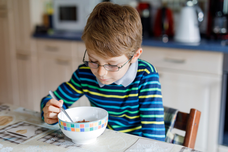 Adorable Happy little blond kid boy with glasses eating homemade cereals for breakfast or lunch. Healthy eating for children. At nursery, at school canteen or at home