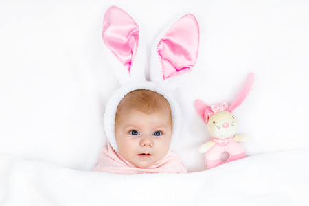 Adorable cute newborn baby girl in Easter bunny costume and ears. Lovely child playing with plush rabbit toy. Holiday concept..