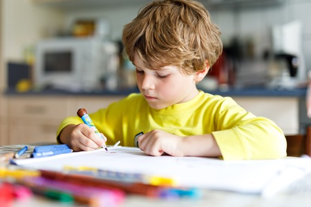 Tired little kid boy at home making homework at the morning before the school starts. Little child doing excercise, indoors. Elementary school and education. Happy blonde kid painting letters. Stok Fotoğraf - 112172816