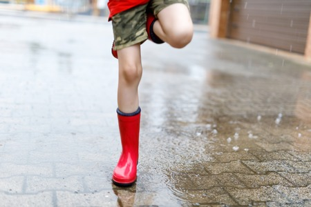 Child wearing red rain boots jumping into a puddle. Close up. Kid having fun with splashing with water. Warm heavy summer rain and happy children