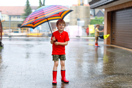 Kid boy wearing red rain boots and walking with colorful umbrella on city street. Child with glasses on summer day. happy kid during heavy summer shower rain.