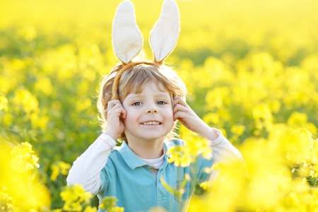 Cute little kid boy with bunny ears having fun with traditional Easter eggs hunt, outdoors. Celebrating Easter holiday. Toddler finding, colorful eggs in yellow flower field..