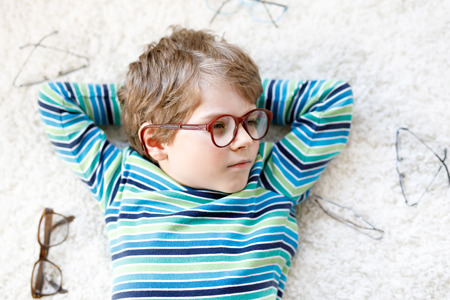 Close-up portrait of little blond kid boy with different eyeglasses on white background. Happy smiling child in casual clothes. Childhood, vision, eyewear, optician store. Boy choosing new glasses.