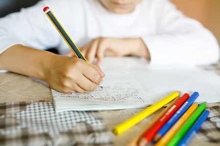 Child doing homework and writing story essay. Elementary or primary school class. Closeup of hands and colorful pencils