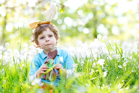 Cute little kid boy with Easter bunny ears celebrating traditional feast. Happy child eating chocolate rabbit fugure on warm sunny day. Family, holiday, spring concept. Toddler sitting between flowers. Stock Photo