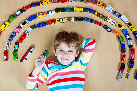 Cute little blond kid boy playing with lots of toy cars indoor. Child wearing colorful shirt. Happy preschooler having fun at home or nursery. Big collection of different vehicles. Happiness game.