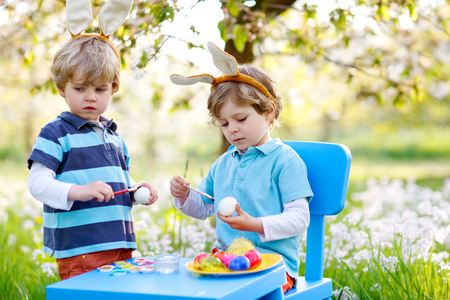Two cute little kid boys wearing Easter bunny ears, painting colorful eggs and having fun outdoors. Family, siblings, brothers, twins celebrating religious holiday. Best friends coloring eggs.