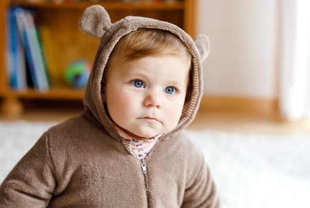 Babymädchen mit blauen Augen mit braunem Bären-Winteroveral im sonnigen Schlafzimmer. Neugeborenes Kind, das für einen Spaziergang im Freien gekleidet wird. Kindergarten für Kinder. Textilien und Bettwäsche für Kinder. Glückliche gesunde Tochter