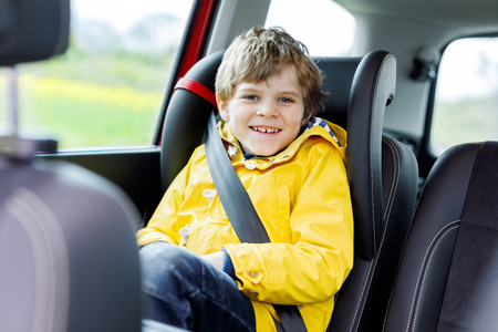Adorable cute preschool kid boy sitting in car in yellow rain coat. Little school child in safety car seat with belt enjoying trip and jorney. Safe travel with kids and traffic laws concept 写真素材 - 112225937