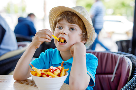 Cute healthy preschool kid boy eats french fries potatoes with ketchup sitting in cafe outdoors. Happy child eating unhealthy food in restaurant