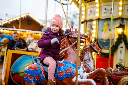 Adorable little kid girl riding on a merry go round carousel horse at Christmas funfair or market, outdoors. Happy child having fun on traditional family xmas market in Nuremberg, Germany