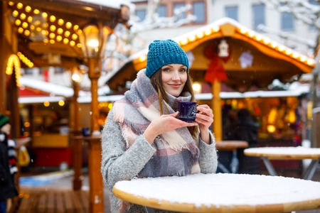 Beautiful young woman drinking hot punch, mulled wine on German Christmas market. Happy girl in winter clothes with lights on background on winter snow day in Berlin, Germany.